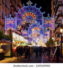 Valencia, Spain, March 2018. Numerous people in the illuminated streets and food stalls, during the Fallas festival in Valencia.