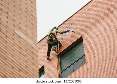 Valencia, Spain - March 5, 2019: Painter perched hanging on the walls of a building with ropes.