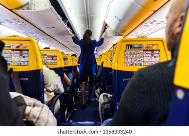 Valencia, Spain - March 8, 2019: Stewardess inside a Ryanair plane securing the top luggage before takeoff, walking down the aisle from behind.