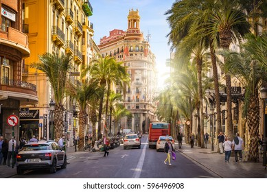 VALENCIA, SPAIN - MARCH 9, 2017: Street in Valencia Spain. Tourists an people passing by. Palm Trees in the always sunny and bright Spanish City of Valencia.