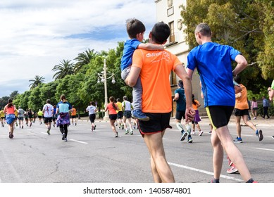 Valencia, Spain - May 19, 2019: Father carrying in his arms his son who participates in a popular running race.