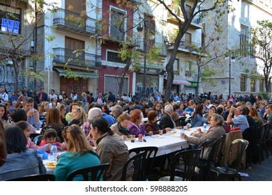 VALENCIA, SPAIN - NOVEMBER 6, 2016. Eating  Paella, traditional Valencian food, on Plaza del Mercado at 100 years since the founding of the central market, Valencia, Spain.