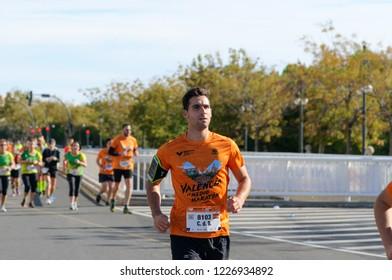 VALENCIA, SPAIN - OCTOBER 28, 2018: Runners participate in Valencia-Trinidad Alfonso EDP Half-Marathon 2018. Athletic man running in t-shirt with official marathon logo