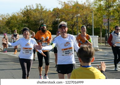 VALENCIA, SPAIN - OCTOBER 28, 2018: Elderly runners participate in Valencia-Trinidad Alfonso EDP Half-Marathon 2018. Senior man and woman giving high-five to young boy
