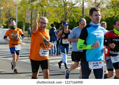 VALENCIA, SPAIN - OCTOBER 28, 2018: Runners participate in Valencia-Trinidad Alfonso EDP Half-Marathon 2018. Happy smiling male participant showing thumb up sign