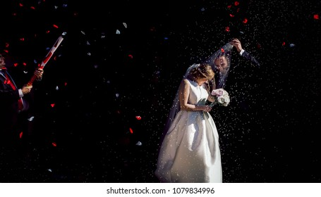 Valencia Spain; October 29 2016; A newly married couple leave the church while their guests receive them with rose petals and rice.