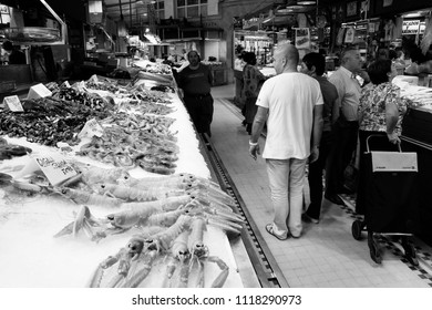 VALENCIA, SPAIN - OCTOBER 8, 2010: People shop at Mercado Central in Valencia, Spain. Historic Mercado Central is one of the oldest markets in Europe still running, popular with tourists.