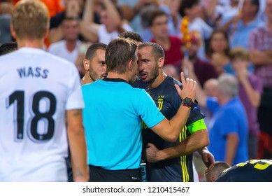 VALENCIA, SPAIN - SEP 19: The referee Felix Brych discusses with Chiellini at the UCL match between Valencia CF and Juventus FC at Mestalla on September 19, 2018 in Valencia, Spain.