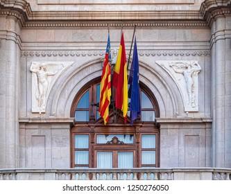 VALENCIA, SPAIN - SEPTEMBER 01, 2018: Three flags of European Union, Spain and Valencia on facade of City Hall building of Valencia.
