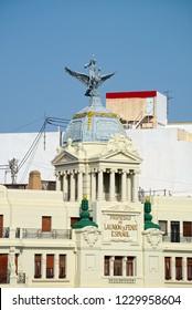 VALENCIA, SPAIN - SEPTEMBER 02, 2018: Sculptures on top of tower of building called Edificio de la Union y el Fenix (The Union and the Phoenix), created in 1929 by architect Enrique Viedma Vidal.