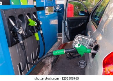 Valencia,Spain - December 11, 2018: Fuel pistols at european Petrol station.  95 E5 fuel  green pistol inserted to the fuel tank of the car. Focus on the pistol.