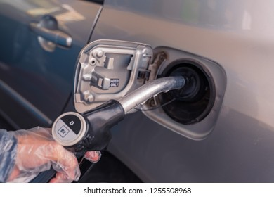 Valencia,Spain - December 11, 2018: Fuel pistols at european Petrol station. Woman's hand  putting Diesel B7 fuel  black pistol to the fuel tank. Focus on the pistol, DD sign out of the