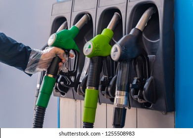 Valencia,Spain - December 11, 2018: Fuel pistols at european Petrol station. Woman's hand in plastic glove taking 95 fuel pistol. Focus on the  hand and the green pistol.