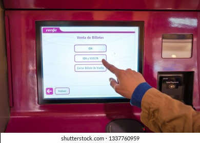 Valencia,Spain - March 09, 2019:   Finger selecting roundtrip on the touchscreen of Renfe ticket terminal. Railway ticket purchase, Spain.