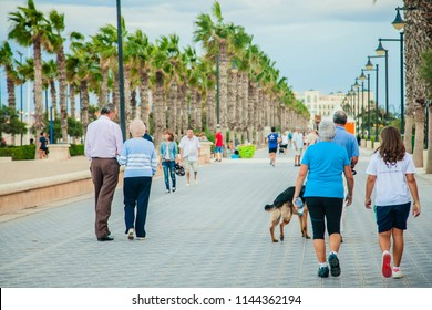Valencia/Spain - September 2012 : Back view of loving senior couple are talking and walking  in promenade in Valencia Spain.The happy old couple in the summer on a walk