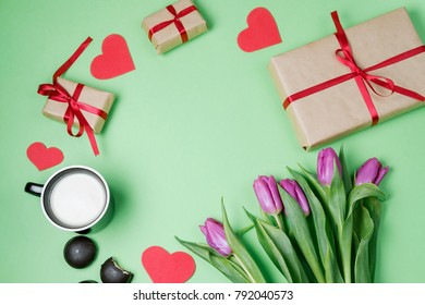 Valentine background with gift box, sweet, hearts and tulips on green table. Top view, flat lay