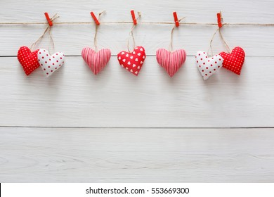 Valentine background with sewed pillow diy handmade hearts row border on red clothespins at rustic white wood planks. Happy lovers day card mockup, copy space