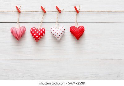 Valentine background with sewed pillow hearts row border on red clothespins at rustic white wood planks. Happy lovers day card mockup, copy space