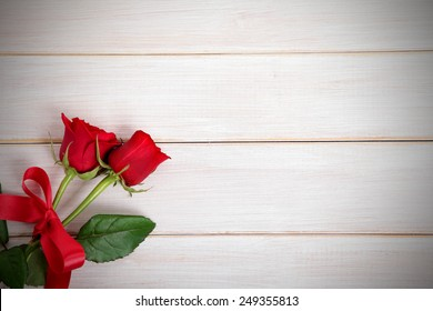 Valentine background of two red roses on  white wood. Space for copy.