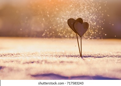 Valentine background - two wooden hearts in beautiful snowflakes in the air