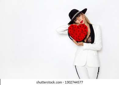 Valentine Beauty, elegant girl with red heart with roses. Portrait of a young female model with gift and hat, isolated on background. Beautiful Happy Young woman presenting flower box.