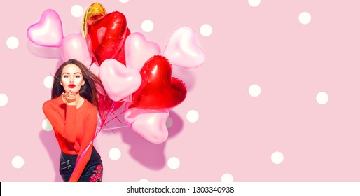 Valentine Beauty girl with colorful air balloons laughing, on pink background. Beautiful Happy Young woman. holiday party. Joyful model having fun, playing and celebrating with red color balloon