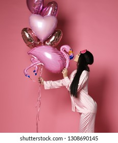 Valentine Beauty girl hold red and pink air balloons hearts blow kiss on pink background. Beautiful Happy Young woman holiday party joyful having fun celebrating Valentine's Day