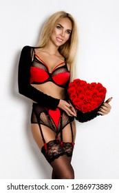 Valentine Beauty girl in lingerie holding red heart with roses. Portrait of a young female model with gift, isolated on background. Beautiful Happy Young woman presenting product. Joyful model