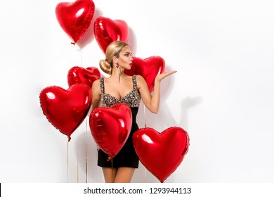 Valentine Beauty girl with red air balloon portrait pointing hand, isolated on background. Beautiful Happy Young woman presenting products. Holiday party, birthday. Joyful model - Image