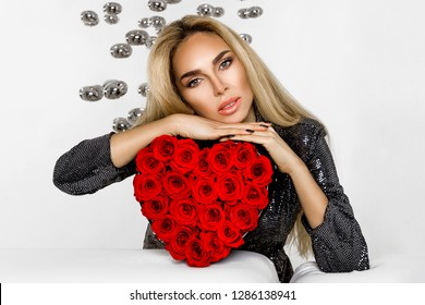 Valentine Beauty girl with red heart roses. Portrait of a young female model with gift, isolated on background. Beautiful Happy Young woman presenting products. Holiday party, birthday. Joyful model