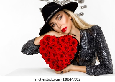 Valentine Beauty girl with red heart roses. Portrait of a young female model with gift and hat, isolated on background. Beautiful Happy Young woman presenting flower box. Holiday party, birthday.