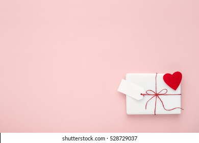 Valentine or birthday white gift with red bow,  blank label decorated with felt heart on pink background. Flat lay. Copy space.