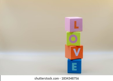 Valentine concept, Stacked colourful wooden alphabet with word LOVE, Multicolour wood cube on antique white colour background with free copyscape.