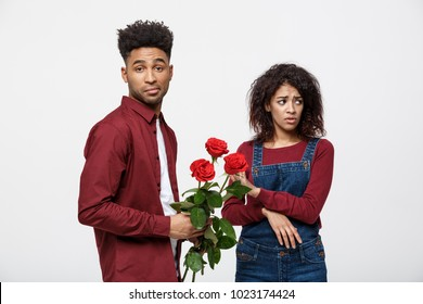 Valentine concept - young african american woman upset and ignore rose from her boyfriend.