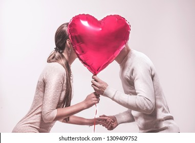 Valentine Couple. Beauty Girl and her Handsome Boyfriend holding heart shaped air balloon and kissing. Happy Joyful Family. Love. Happy Valentine's Day celebrating