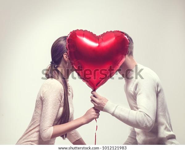 Пара Валентина. Красота девушка и ее красивый парень держит в форме сердца воздушный шар и поцелуи. Счастливая радостная семья. Люблю. С Днем Святого Валентина