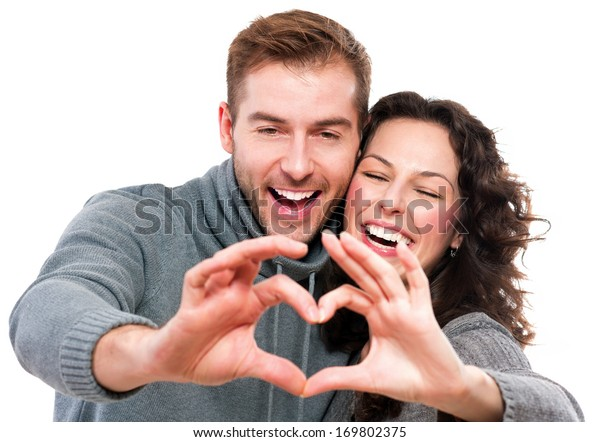 Valentine Couple. Portrait of Smiling Beauty Girl and her Handsome Boyfriend making shape of Heart by their Hands. Happy Joyful Family. Love Concept. Heart Sign. Laughing Happy Lovers. Valentines Day