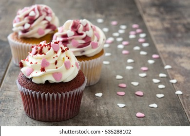 Valentine cupcakes decorated with sweet hearts on wooden table