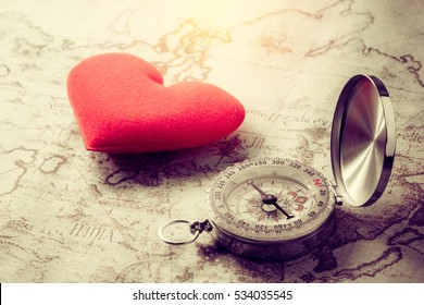 Valentine day background. Compass and love red heart on vintage map. Finding real love concept