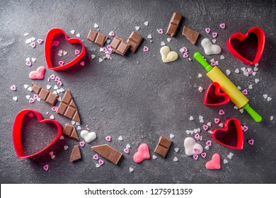 Valentine day baking concept, sweets and baking cooking background for Valentine`s day, with rolling pin, cookie cutters, sugar sprinkling, chocolate. Black concrete table top view copy space