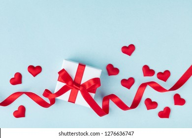 Valentine day card or banner. Gift or present box and red heart on blue background. Flat lay.
