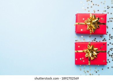 Valentine day composition, Greeting gift box with gold confetti on blue background. Flat lay