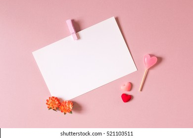 Valentine day composition: stationery / photo template with clamp, small hearts, candy and spring flowers on light pink background. Top view.