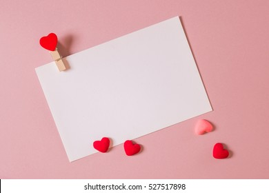 Valentine day composition: stationery / photo template with clamp and small hearts on light pink background. Top view.