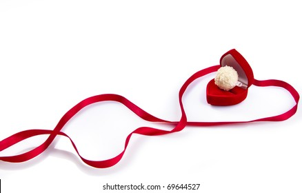 Valentine day concept: candy in red heart-shape gift-box and red satin ribbon. Macro shot, isolated on white background