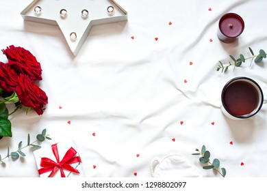 Valentine day concept frame on the white blanket . Holiday top view card with red roses. Copy space