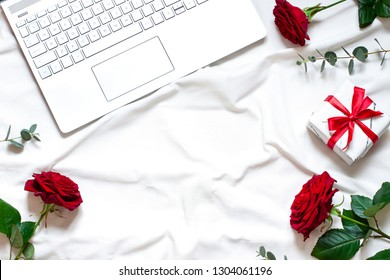 Valentine day concept frame on the white blanket  with a laptop. Holiday top view card with red roses. Copy space