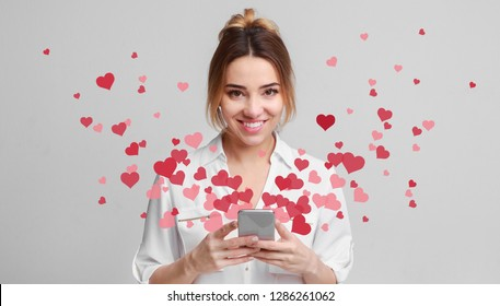 Valentine day concept, love message - hearts flying out smartphone in womans hands