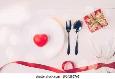 Valentine day concept, wineglass and red ribbon and utensil put in heart on white wooden table background with bokeh, champaign glass on wood desk, couples wine glass together, holiday concept.