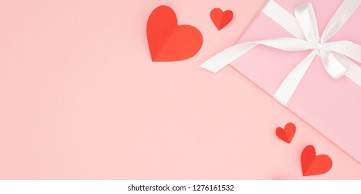 Valentine day idea composition: pink gift box with white ribbon and small red hearts on paper coral background. Top view. Love day concept flat lay.